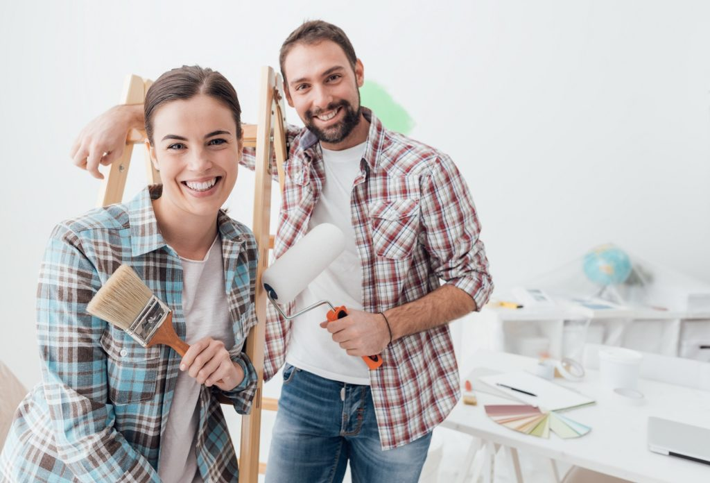 Creative young couple remodeling their house and painting walls, they are posing together and smiling at camera