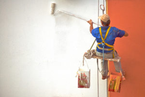 Professional painting contractor painting walls with white and orange as he sits on a swing-like seat to keep him in position to paint.