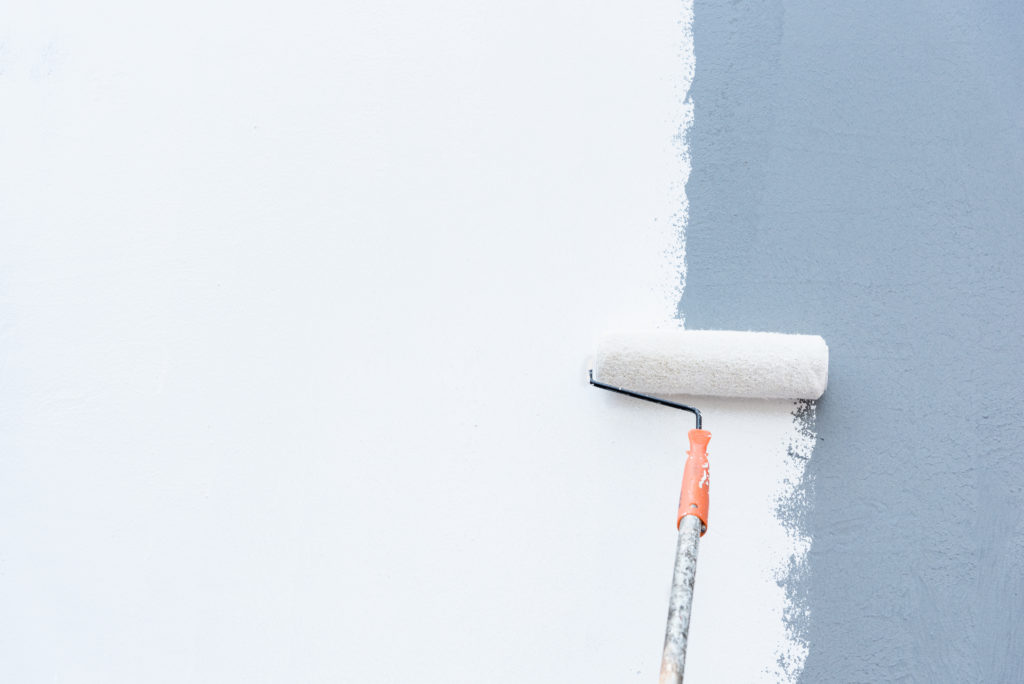 Roller brush applies a fresh coat of white paint over a light blue wall surface.